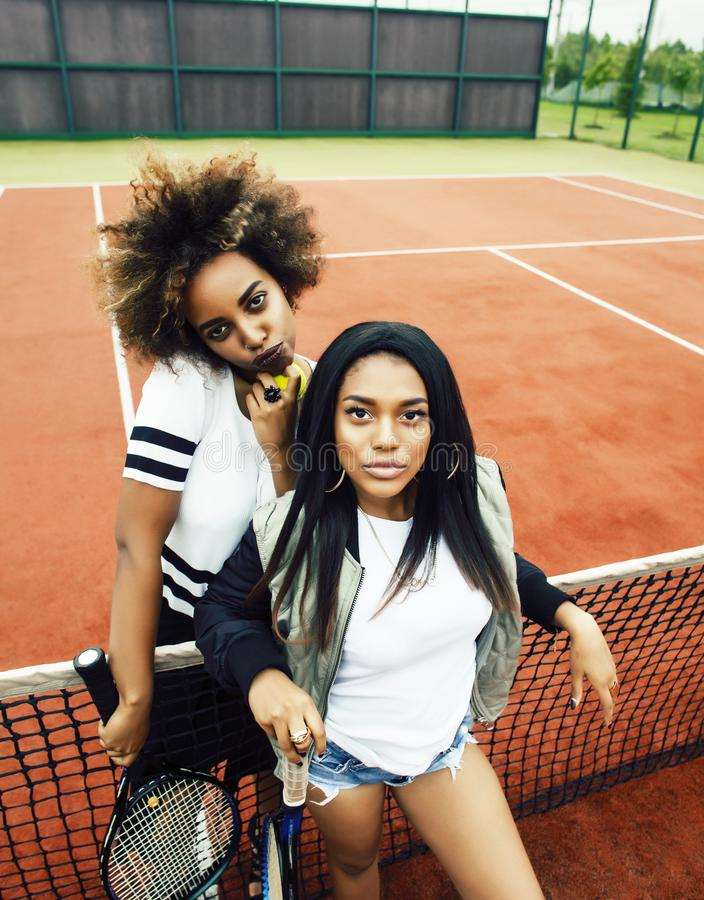 Young pretty girlfriends hanging on tennis court, fashion stylish dressed swag, best friends happy smiling together stock photos