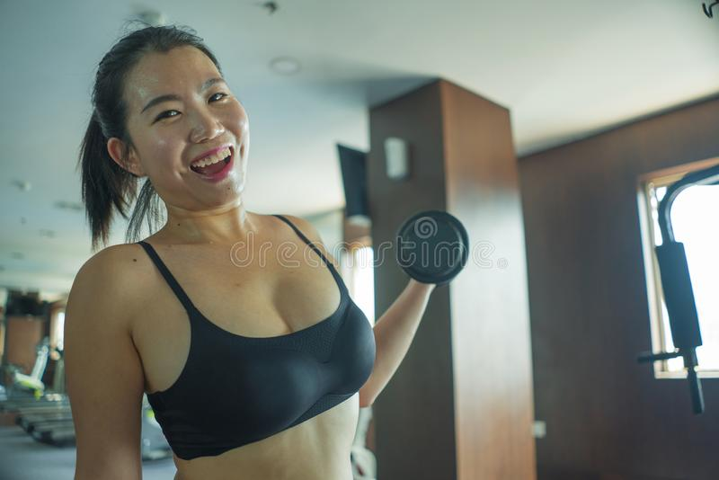Young pretty and happy Asian Chinese woman working hard at hotel gym or fitness center lifting dumbbell doing body building. Indoors workout in healthy royalty free stock photos