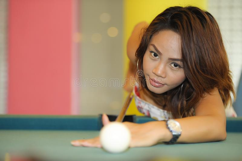 Young pretty and happy Asian girl playing snooker holding stick at pool table in night club or bar. Wearing dress stock photos