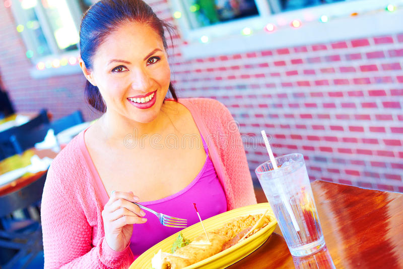 Young Pretty Happy Mixed Race Woman Eating Chimichanga royalty free stock images