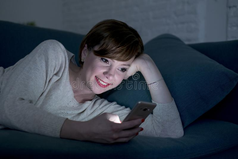 Young pretty and happy red hair woman on her 20s or 30s lying on home couch or bed using mobile phone late at night smiling relaxe stock photos