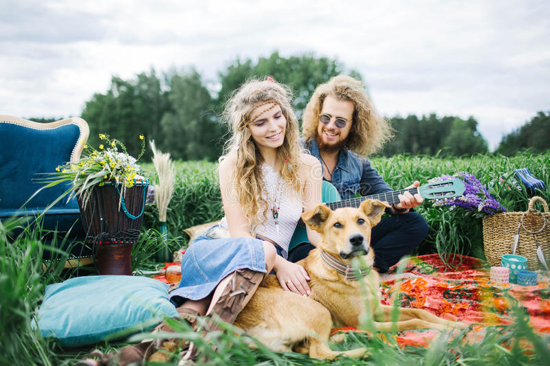 Young pretty hippie couple with guitar and dog outdoor. Young pretty curly hippie couple with guitar and dog outdoor royalty free stock photos