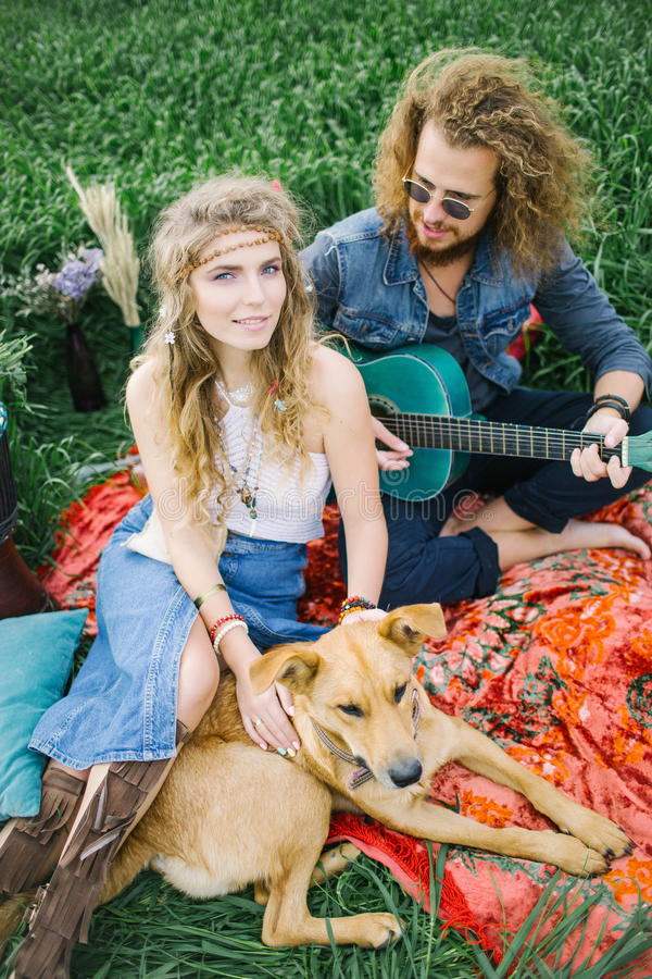 Young pretty hippie couple with guitar and dog outdoor. Young pretty curly hippie couple with guitar and dog outdoor royalty free stock images
