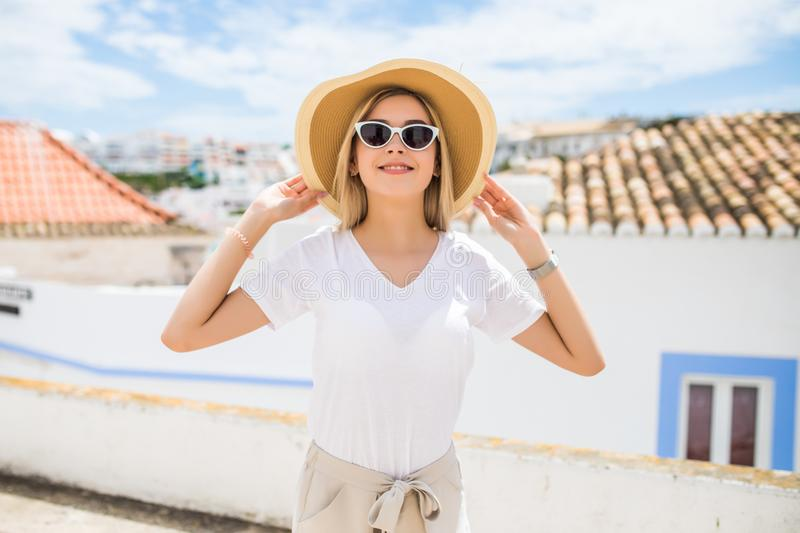 Young pretty hipster cheerful girl posing on the street at sunny day, having fun alone, stylish vintage clothes hat and sunglasses stock image