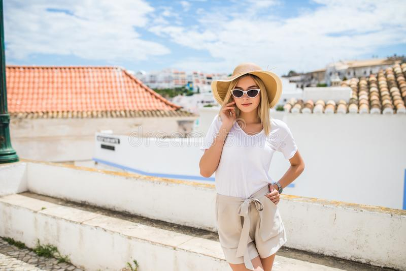 Young pretty hipster cheerful girl posing on the street at sunny day, having fun alone, stylish vintage clothes hat and sunglasses royalty free stock photography