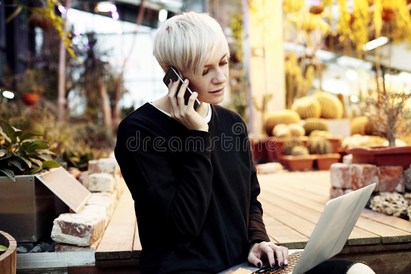 Young pretty hipster woman with blonde short hair sitting on stairs, talking by mobile phone working on laptop. royalty free stock photos