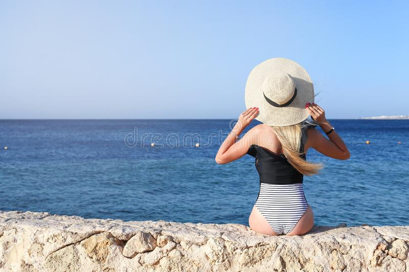 Young pretty hot sexy woman relaxing in swimsuit on stones with blue sea and sky on background. Summer Vacation Concept. Back View.  royalty free stock photos