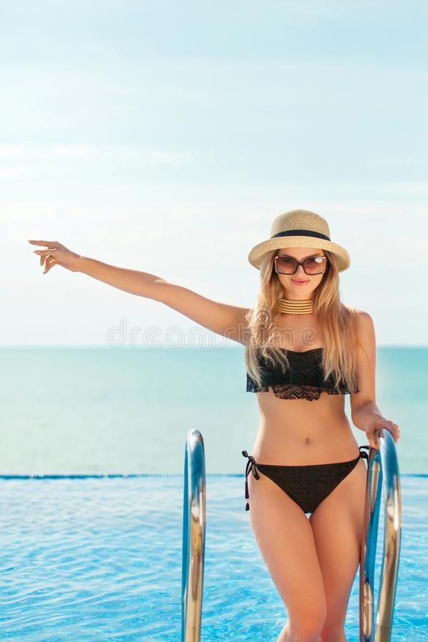 Beautiful fit woman in black swim suit and hat posing on the beach. Summer vacation. Model pointing on copy space. stock photo