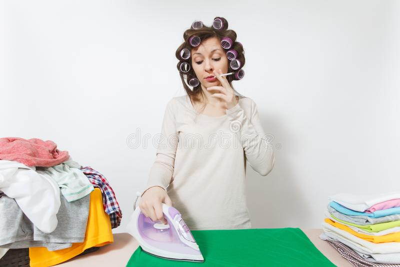 Young pretty housewife. Woman isolated on white background. Housekeeping concept. Copy space for advertisement. Distressed fun housewife with curlers on hair in royalty free stock photo