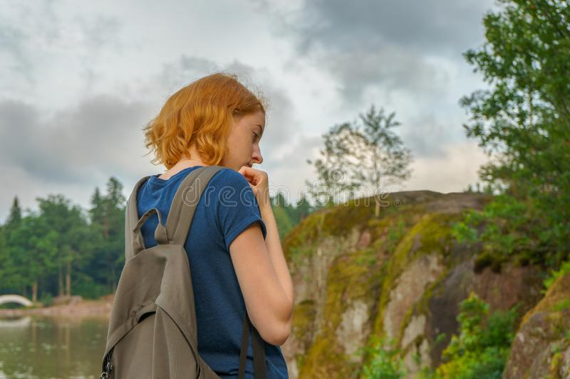 Young pretty lady with backpack walking outdoors in summer evening. Tourist on the beautiful landscape background. royalty free stock photo