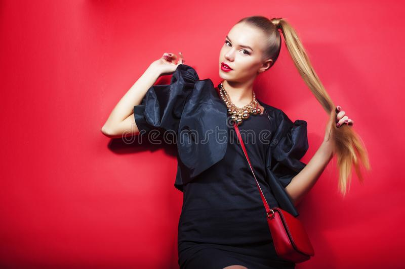 Young pretty lady in black suit and small handbag posing on red background, lifestyle people concept royalty free stock images