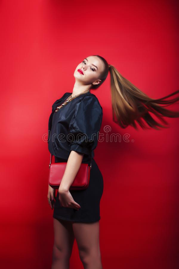 Young pretty lady in black suit and small handbag posing on red background, lifestyle people concept stock photography