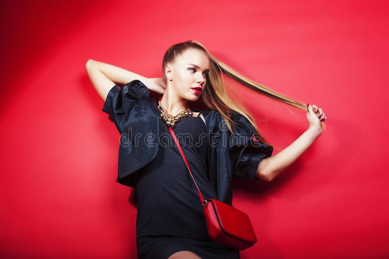 Young pretty lady in black suit and small handbag posing on red background, lifestyle people concept stock image