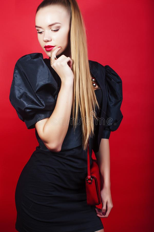 Young pretty lady in black suit and small handbag posing on red background, lifestyle people concept royalty free stock photo