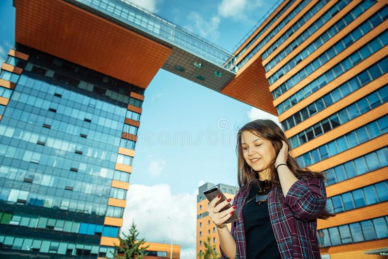 Young pretty long-haired brunette in a plaid shirt stands on city street and communicates with smartphone. Beautiful girl shoots royalty free stock image