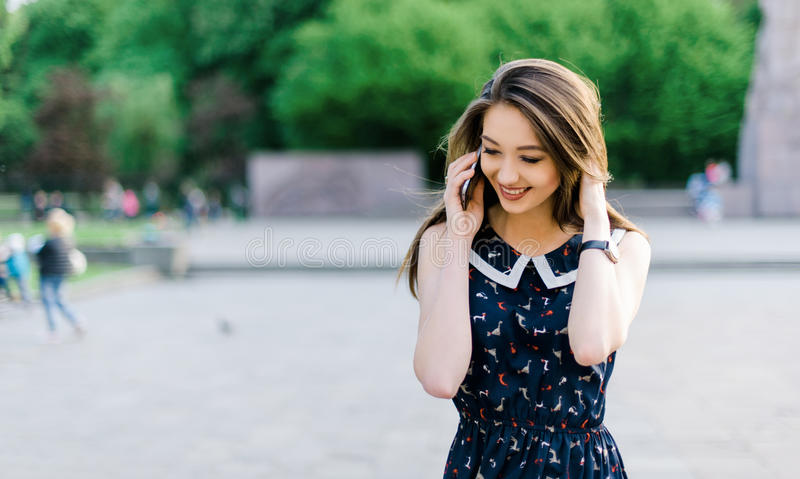 Young pretty long-haired brutette woman talking by phone in the city park royalty free stock image