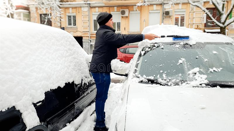 Pictere of young pretty man in black coat and hat trying to clean up snow covered car after blizzard with black brush royalty free stock image