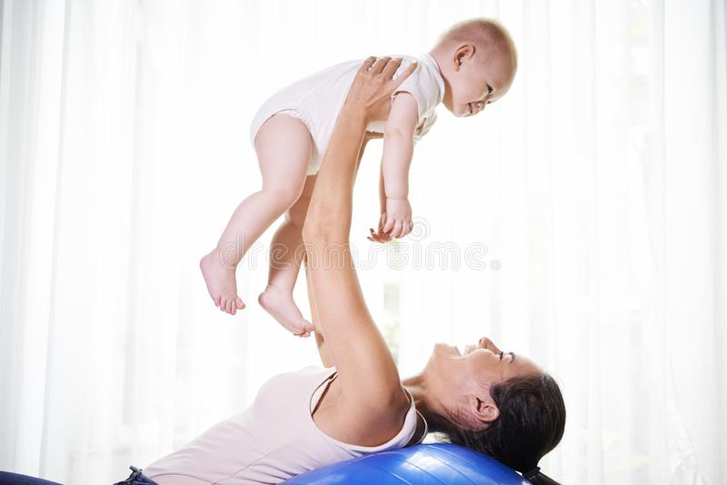 Mother lifting her baby. Young pretty mixed-race women lifting her baby when exercising on fitness ball at home royalty free stock photo