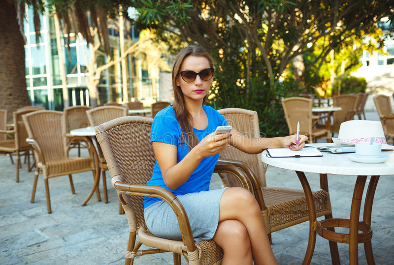 Download Young Pretty Modern Blogger Using Smartphone And Makes Notes In Stock Photo - Image of cafeteria, girl: 62421996