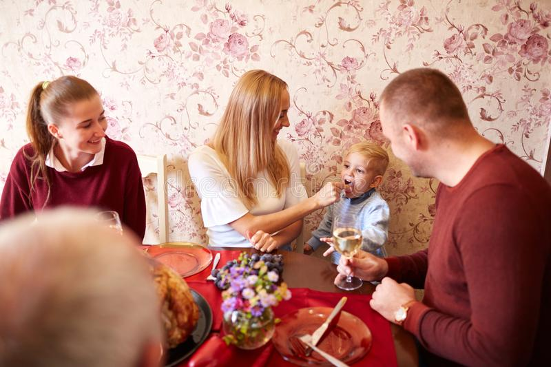 Happy mom and son at the Christmas or Thanksgiving dinner on a festive background. Family bonding concept. Young, pretty mother feeding happy son with sweets at royalty free stock photography