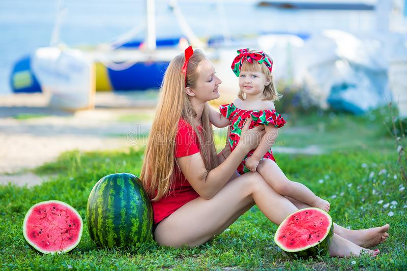 Young pretty mother playing with her little cute daughter at the beach. Loving mom having fun with her child at the sea shore with royalty free stock image