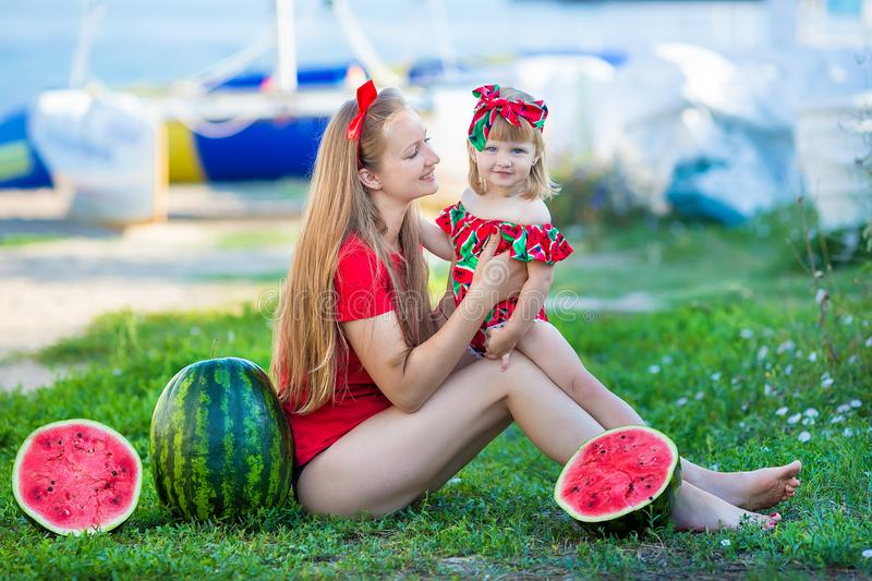 Young pretty mother playing with her little cute daughter at the beach. Loving mom having fun with her child at the sea shore with royalty free stock photography