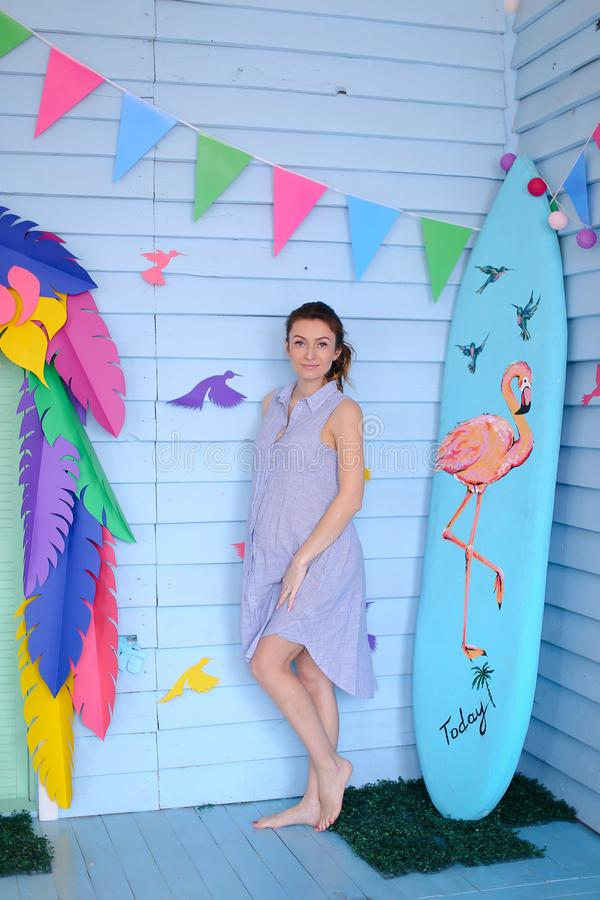 Young pretty pregnant woman standing near surfboard and decorated children house. stock photography