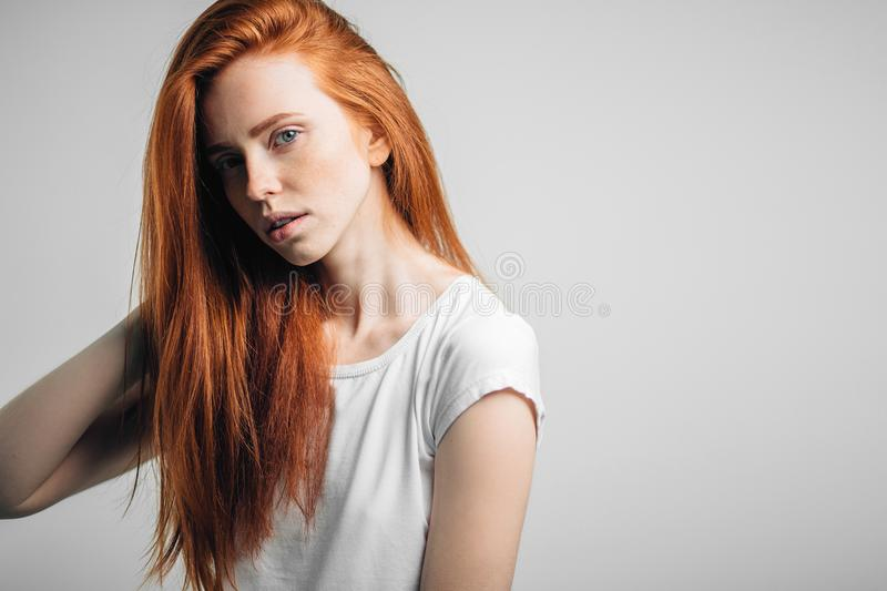 Young pretty redhead girl with freckles looking at camera smiling touching hair stock photos
