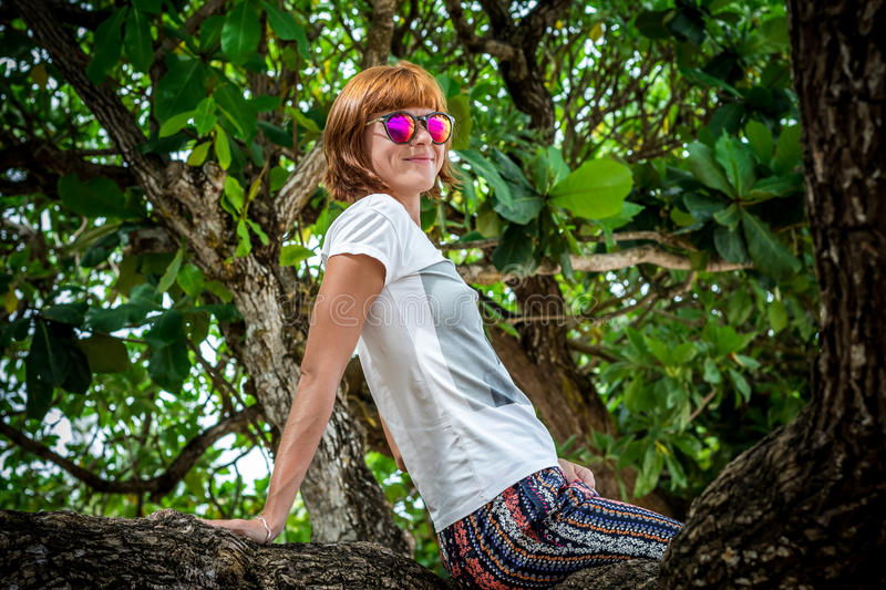Young pretty woman in sunglasses in the summer park of tropical Bali island, Indonesia. Sunny day, smile, happy stock image