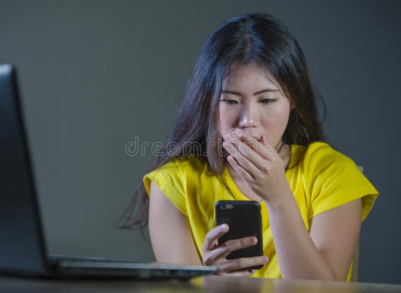 Young pretty shocked and surprised Asian Korean woman looking stressed at mobile phone feeling worried and scared in cyber bullyin royalty free stock photos