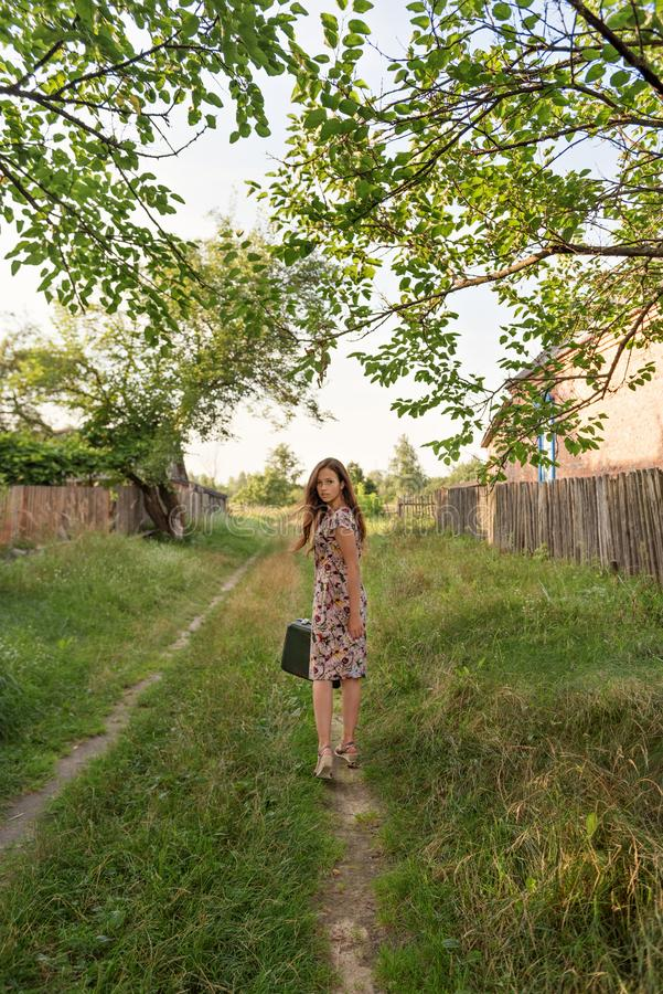 A young pretty slender girl walks along an abandoned rural road with a retro suitcase wrapping her hair fluttering royalty free stock photography