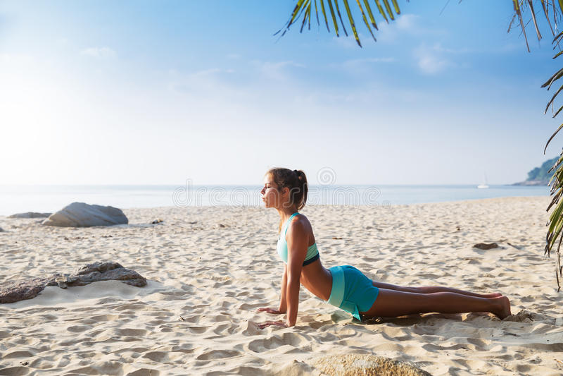 Young pretty slim brunette woman practise yoga pose tropical beach. Young pretty slim brunette woman practise Upward facing dog Urdhva Mukha Svanasana yoga pose royalty free stock photos