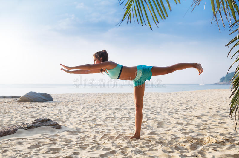 Young pretty slim brunette woman practise yoga pose tropical beach. Young pretty slim brunette woman practise yoga Warrior on foot Virabhadrasana straight pose stock images
