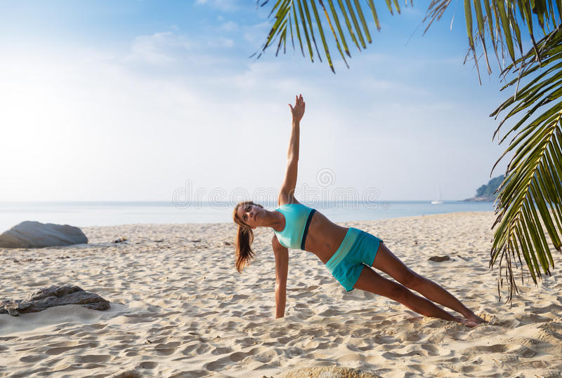 Young pretty slim brunette woman practise yoga pose on tropical. Young pretty slim brunette woman practise yoga Half side plank on hand, legs crossed royalty free stock image