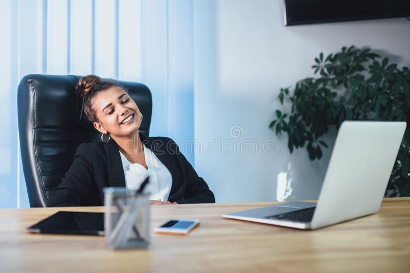 Young pretty smart business girl works in the office. During this, she concluded a profitable contract with her eyes glad royalty free stock image