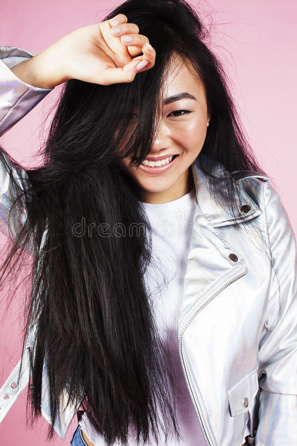 Young pretty smiling asian korean girl wearing modern fashion clothers on pink background, lifestyle people concept stock photography