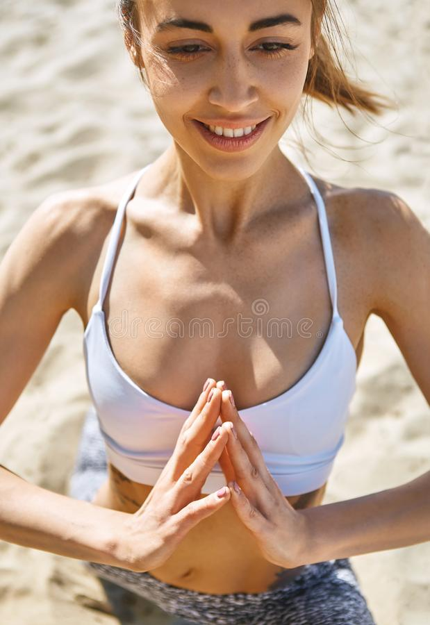 Young pretty smiling woman relaxing practicing yoga and meditation on the sand beach at hot sunny summer day. stock images