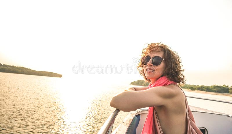 Young pretty solo woman traveler at sunset on boat trip stock photos