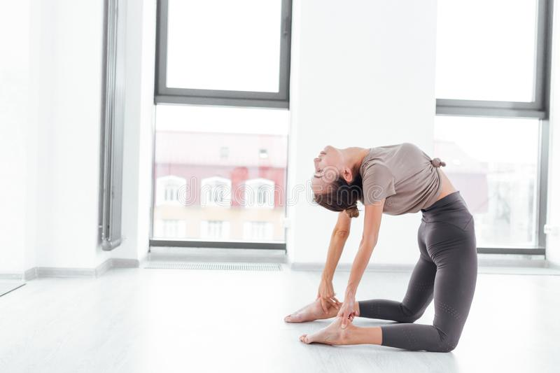 Young pretty talented fit athlete doing backbend stock photography