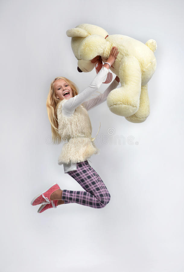 Young pretty teenage girl happy jumping with big teddy bear smil. Ing screaming stock photos