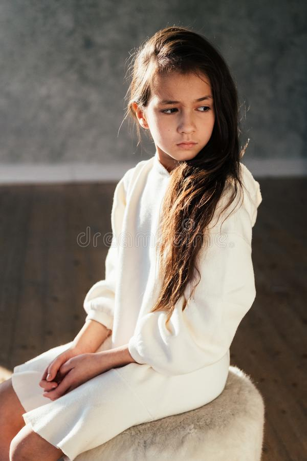 Young pretty teenage girl with sad emotions looking down. Close up portrait stock images