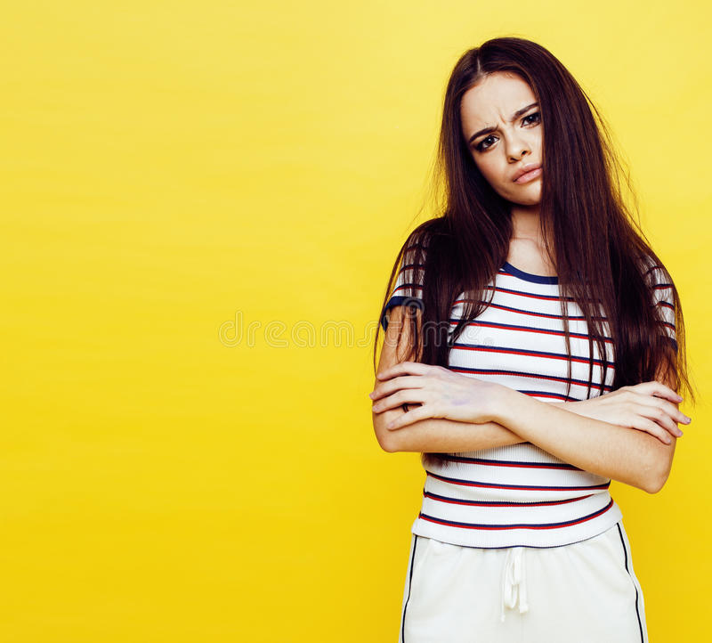Young pretty teenage woman angry posing on yellow background, fashion lifestyle people concept royalty free stock image