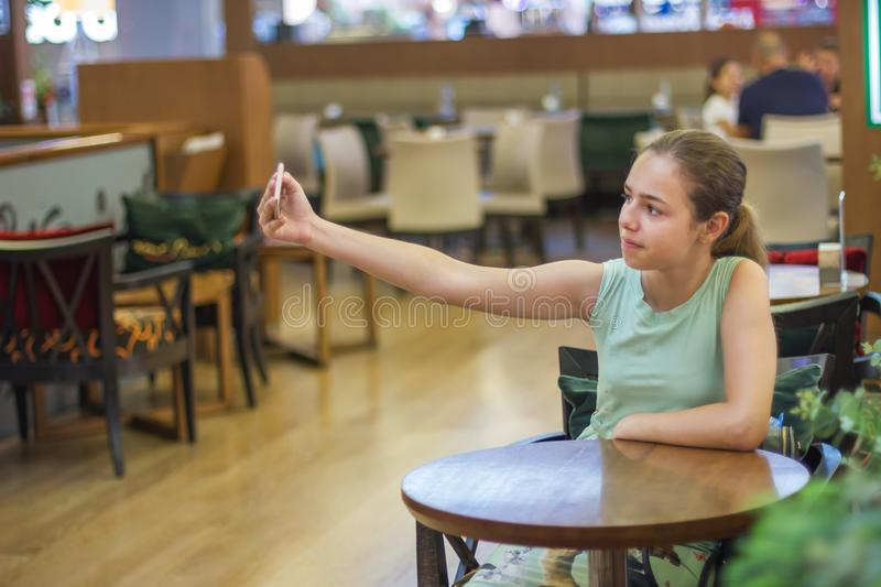 Young pretty teenager girl takes selfie in a cafe at shopping mall stock photography