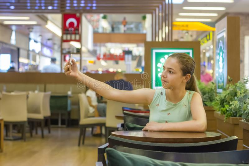 Young pretty teenager girl takes selfie in a cafe at shopping mall stock image