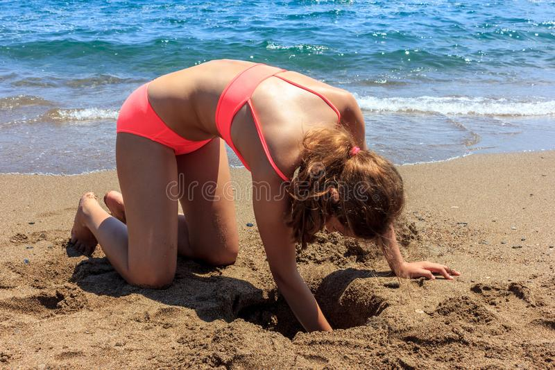 Young pretty teenager tanned girl building a sand castle on the beach near by sea stock photos