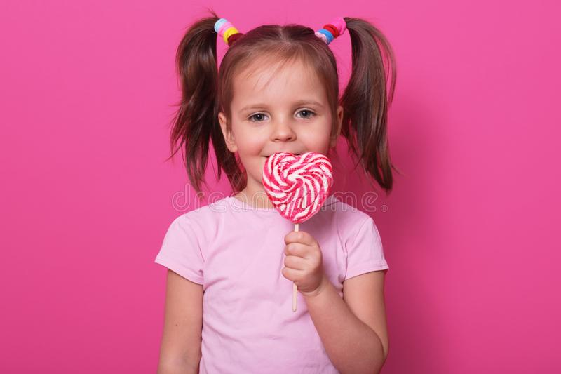 Young pretty toddler girl kid with big sweet lollypop candy in rose casual t shirt posing  over pink studio background, stock photos