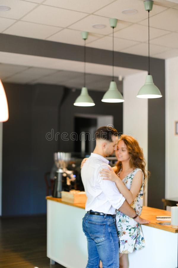 Young pretty wife hugging husband at cafe. Young pretty wife hugging husband at cafe near bar. Concept of happy couple and contemporary interior stock photo