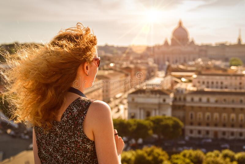 Young pretty woman admiring the view of Rome, Italy, Europe. Beautiful sunny skyline of Rome in summer. Girl tourist looks at Roma royalty free stock photos