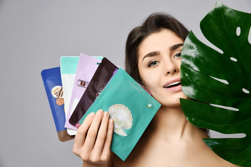 Young pretty woman antcipating pleasure of taking care of herself holds a set of packed cosmetic masks and a large green leaf. Young happy woman antcipating stock photos