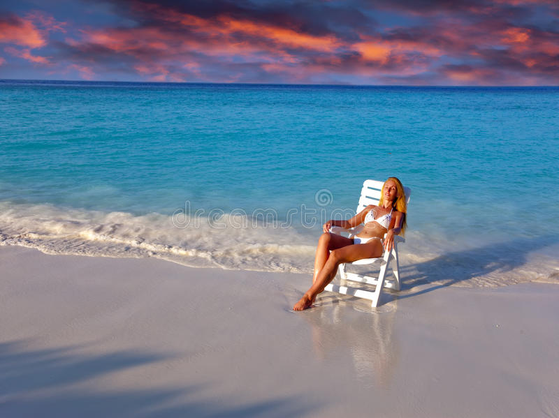 Young pretty woman in a beach chair at ocean royalty free stock photography